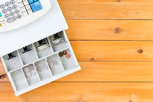 istock Nearly empty cash register drawer on table 598171460