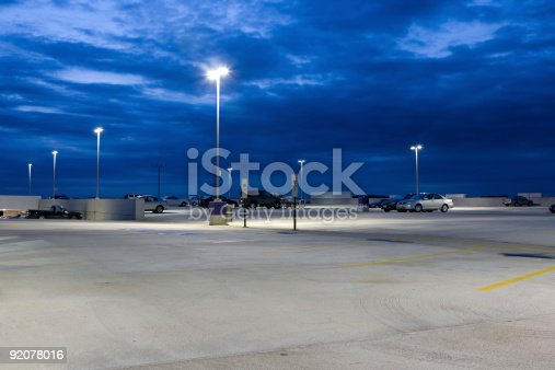 Lamps illuminate this view of a parking lot at dusk