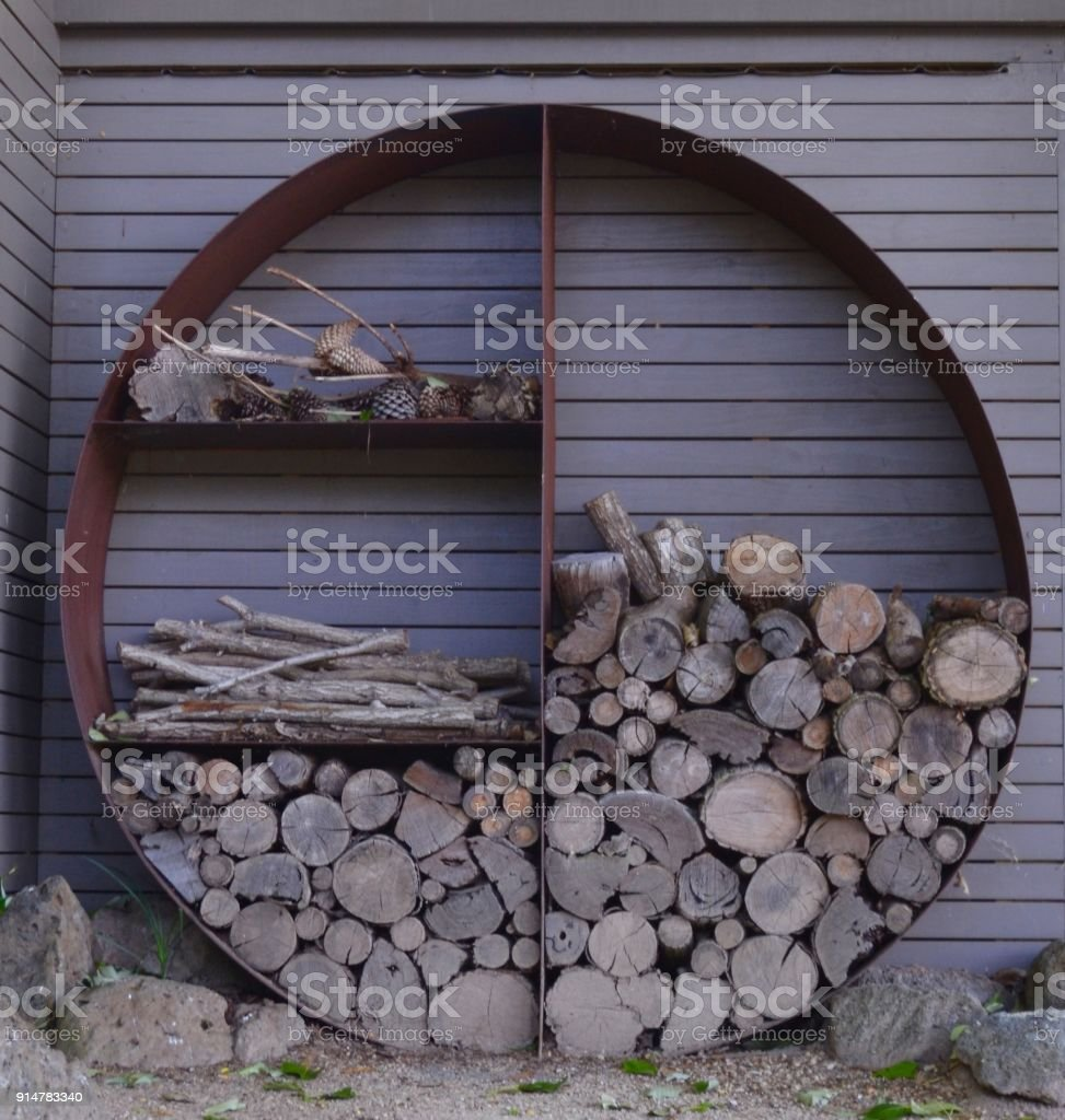 Neat and symmetric stacked wood pile on grey background at spa stock photo