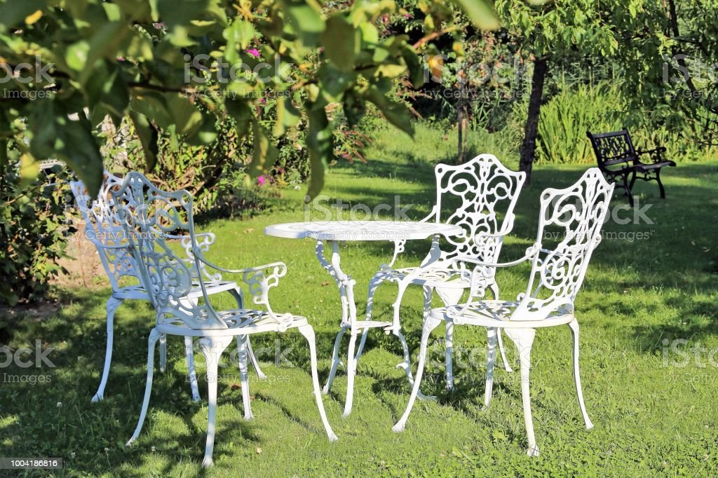 Neat and tidy fruit garden with garden furniture in antique design