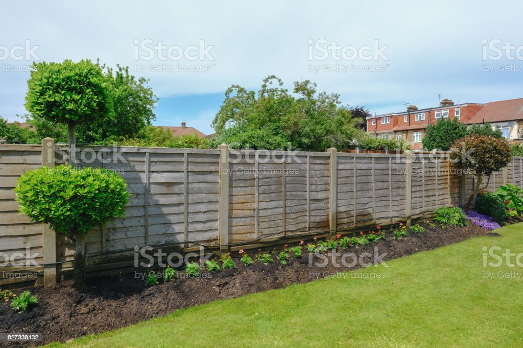 Neat flower bed with garden fence and lawn. stock photo