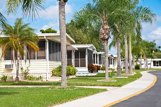 Neat home park full of mobile homes Mobile homes in a row located in a mobile home park in the tropics. Street view with palm trees and sidewalk. Caravan park. trailer park stock pictures, royalty-free photos & images