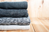 A neat pile of knitted warm blanket or sweaters gray, white on a wooden background.