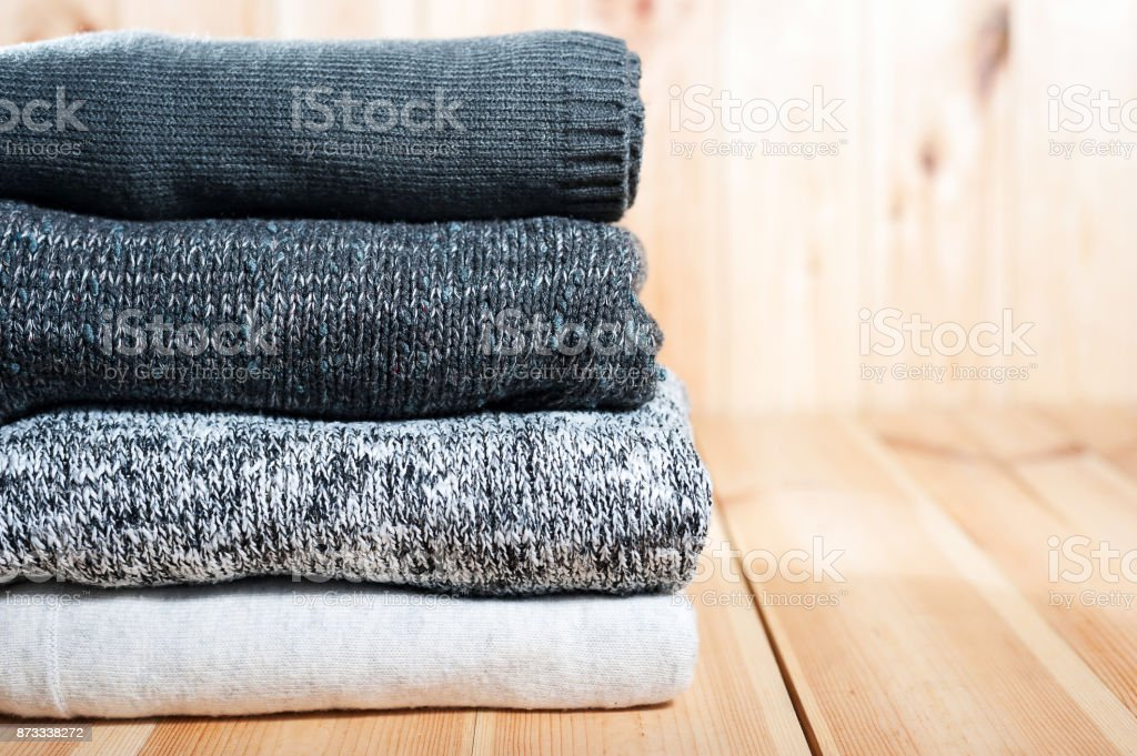 A neat pile of knitted warm blanket or sweaters gray, white on a wooden background. stock photo