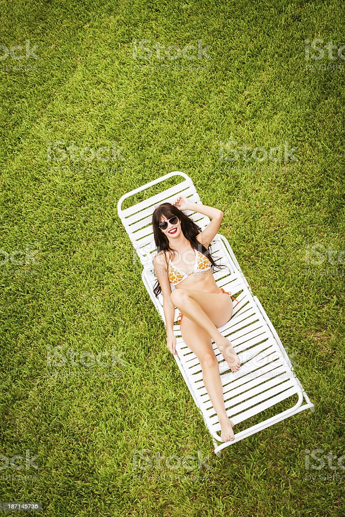 Neat young woman on lawn chair royalty-free stock photo