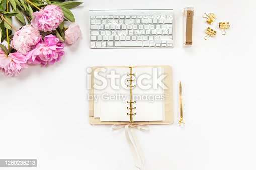 Neatly arranged office stationery with modern gadgets, devices, coffee and flowers on white desk. Top view of school or office supplies. Envelope with useful copy space ready for text or logo.