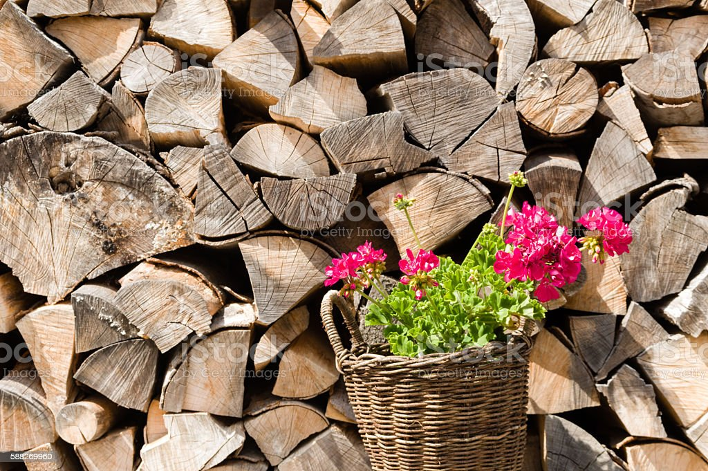 Woven basket with pink flowers in front of a stockpile of neatly...