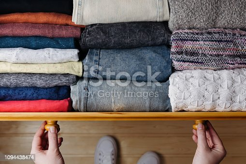Overhead shot of neatly ordered clothes in wooden drawer. Woman organizing clothes in drawer