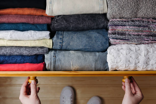 Neatly ordered clothes in drawer Overhead shot of neatly ordered clothes in wooden drawer. Woman organizing clothes in drawer arrangement stock pictures, royalty-free photos & images