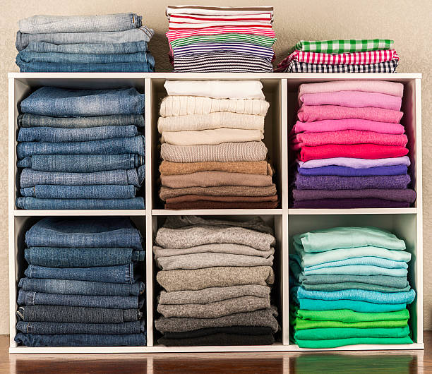 neatly organized womens clothing in white cubicles - ordre photos et images de collection