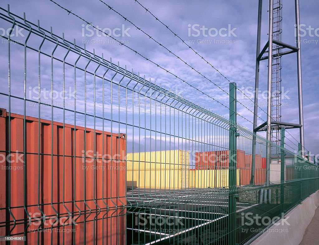 Neatly stacked cargo containers behind wire fence. royalty-free stock photo
