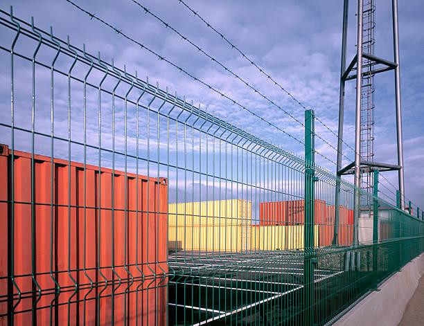 ordentlich angeordnet cargo container hinter draht zaun. - maschendrahtzaun preis stock-fotos und bilder