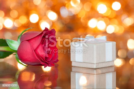 istock Neatly wrapped gift next to rose 509351020