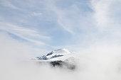 Una cima delle Alpi Marittime spunta dalle nebbie mattutine in inverno