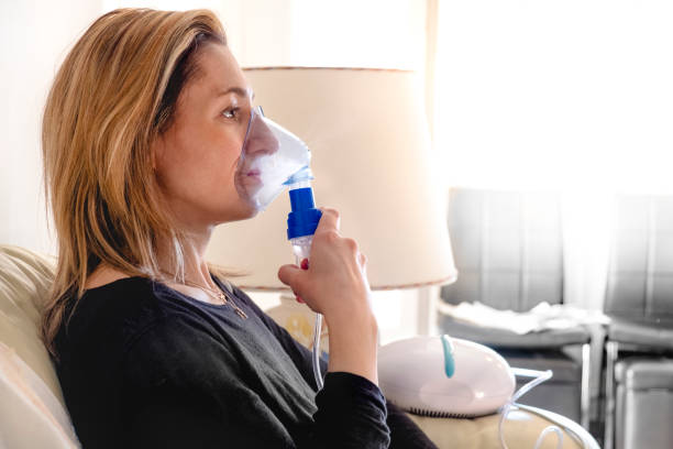 nebulizer aerosol woman inhaler machine medicine at home nebulizer aerosol woman inhaler machine medicine at home . smoke inhalation stock pictures, royalty-free photos & images