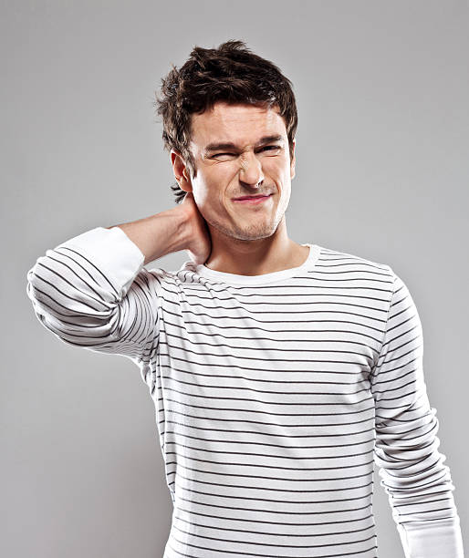 Neck ache Portrait of young man suffering from neck ache. Studio shot, grey background. grimacing stock pictures, royalty-free photos & images