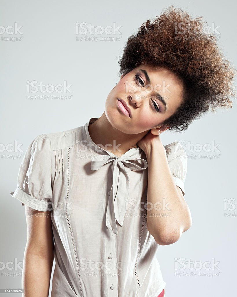 Neck ache Portrait of teenaged afro girl suffering from neck ache. Studio shot, grey background. 18-19 Years Stock Photo