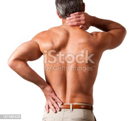 rear view of a shirtless 40-45 year old male holding his neck and lower back in pain.