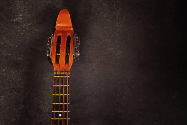 pescoço de um instrumento de cordas bandolim em um fundo escuro com espaço de cópia para o seu texto - foto de acervo