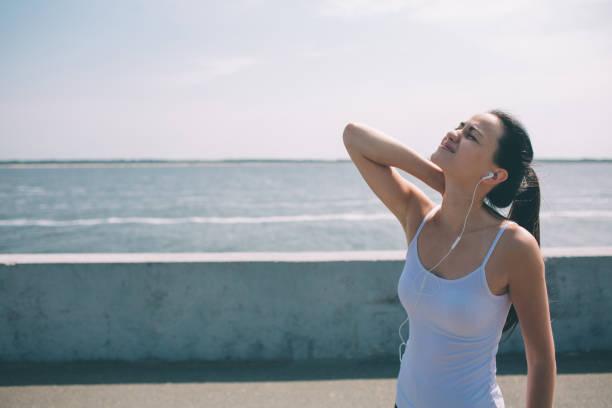 nackenschmerzen beim training. athlet laufen. kaukasisch schwarze haar-läuferin mit sportverletzung. sie berührt die oberschweinmuskulatur nach dem training im sommer nach außen - hals übungen stock-fotos und bilder