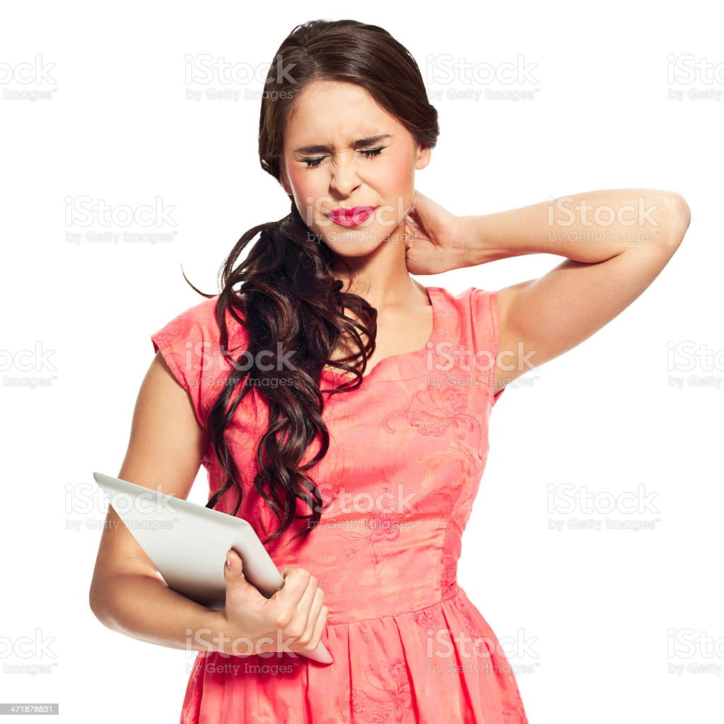 Neck pain Portrait of young woman holding a digital tablet in hand and rubbing her aching neck. Studio shot, white background. 20-24 Years Stock Photo