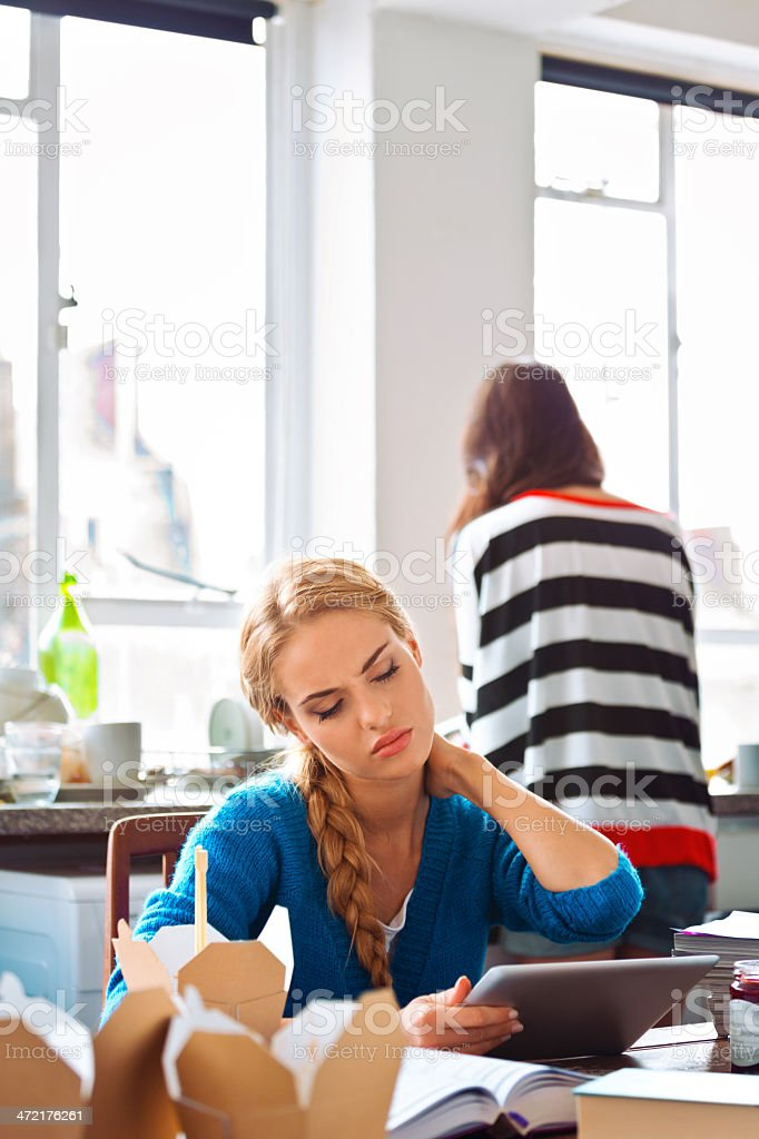 Neck pain Focus on worried young woman sitting at the kitchen table holding a digital tablet and touching her aching neck with her friend standing in the background. 20-24 Years Stock Photo