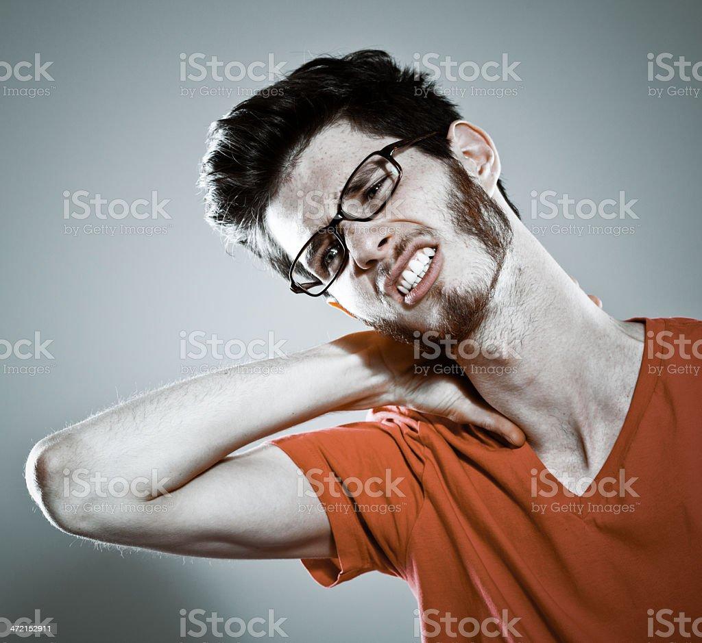 Neckache Portrait of young man suffering from nechache .Studio shot, grey background. 20-29 Years Stock Photo