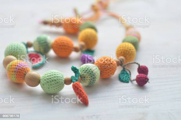 Necklace made from knitted beads and toys for the baby sitting in a picture id956795178?b=1&k=6&m=956795178&s=612x612&h=zvfbfqvsbkh89cajya3jl6h7dnjnws 5baw6dz5tt38=