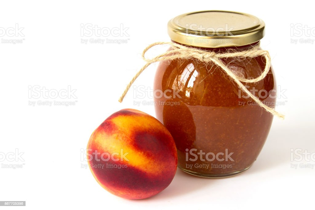 Nectarine jam in a glass jar and fresh peaches on white background stock photo