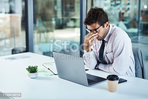 Shot of a businessman looking stressed while sitting at his desk