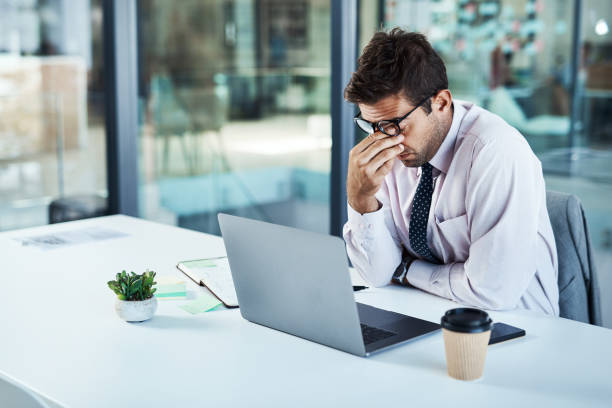 I need a break... Shot of a businessman looking stressed while sitting at his desk mental burnout stock pictures, royalty-free photos & images
