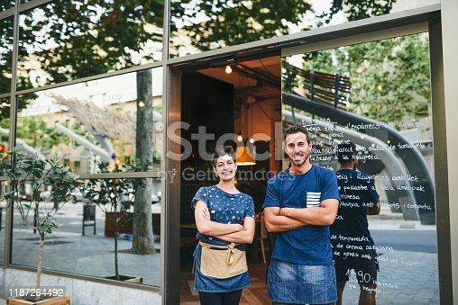 Shot of a confident man and woman standing at the entrance of their cafe