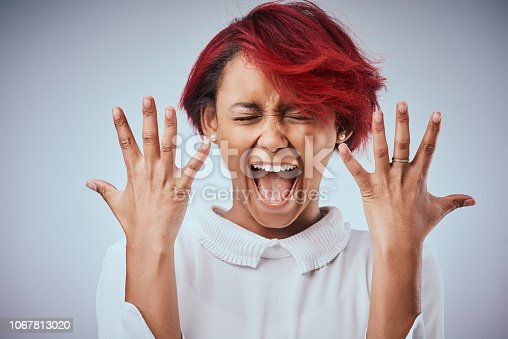 Studio shot of an attractive young woman screaming against a gray background