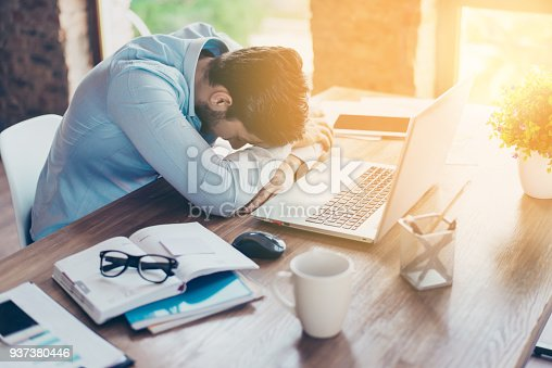 istock I need a vacation! Close up top view portrait of tired sick young brunet guy. He is wearing the formalwear, resting at the workplace 937380446