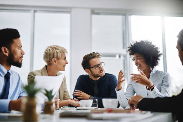 I need everyone to give me their best ideas Shot of a group of businesspeople sitting together in a meeting collaboration stock pictures, royalty-free photos & images