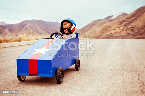 A young boy takes to the slope with his box car to test the limits of speed.