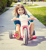 Adorable little girl on a hot wheels style low rider bike, a tricycle. She is thrilled, smiling, joyful, and pedaling fast. Childhood classic that is relatable and full of good energy.