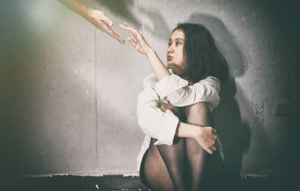 Need Help, Depressed and frustrated, Supporter reaching hand to sad woman in the dark room, Mental health concept. stock photo