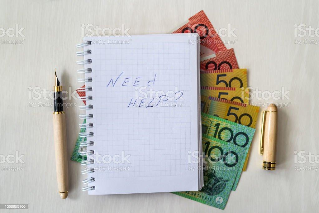 'Need help' text on notepad and australian dollars stock photo