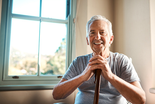 Cropped portrait of a happy senior man sitting and holding his walking stick in a nursing home during the morning
