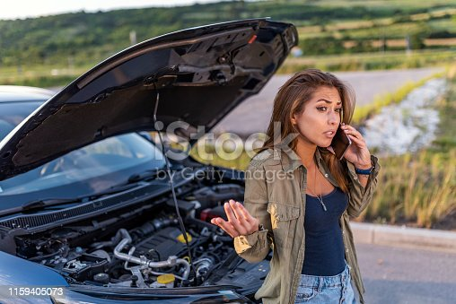 Photo of a Caucasian woman using a smartphone in front of her broken car on the road. Contacting car technician or need help concept. A young sad woman calling a car repair service with her phone, she is having a car breakdown in a countryside road