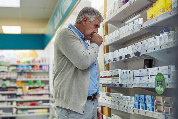 I need something to clear up this cough Shot of a mature man browsing the shelves of a pharmacy and coughing only mature men stock pictures, royalty-free photos & images
