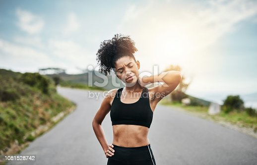 Shot of a sporty young woman holding her neck in pain while exercising outdoors