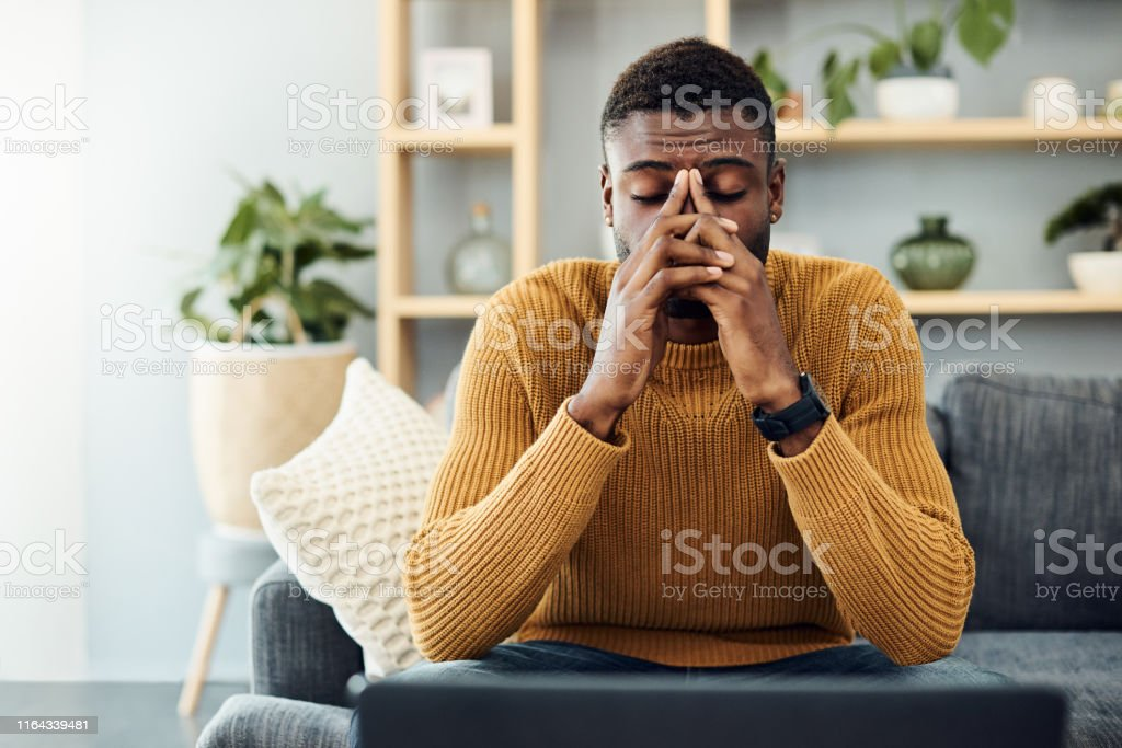 I need to find a way to cope with this stress Shot of a young man looking stressed out at home 20-29 Years Stock Photo