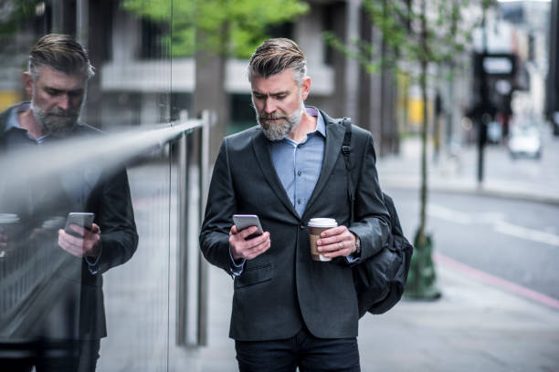 I need to get to the meeting asap A businessman walking to work with his smart phone and a cup of coffee in his hands ASAP stock pictures, royalty-free photos & images