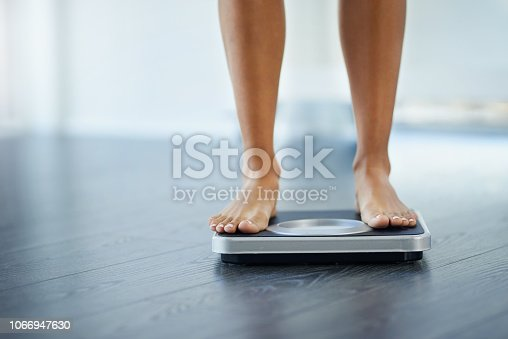 Shot of an unrecognizable woman weighing herself at home