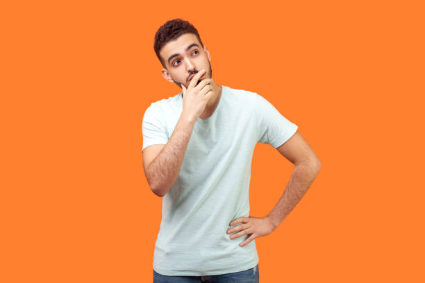 Need to think. Portrait of thoughtful brunette man holding his chin and pondering idea. indoor studio shot isolated on orange background stock photo