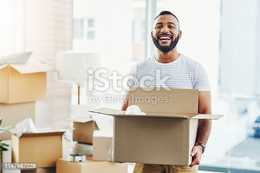 Portrait of a young man carrying a box while moving house