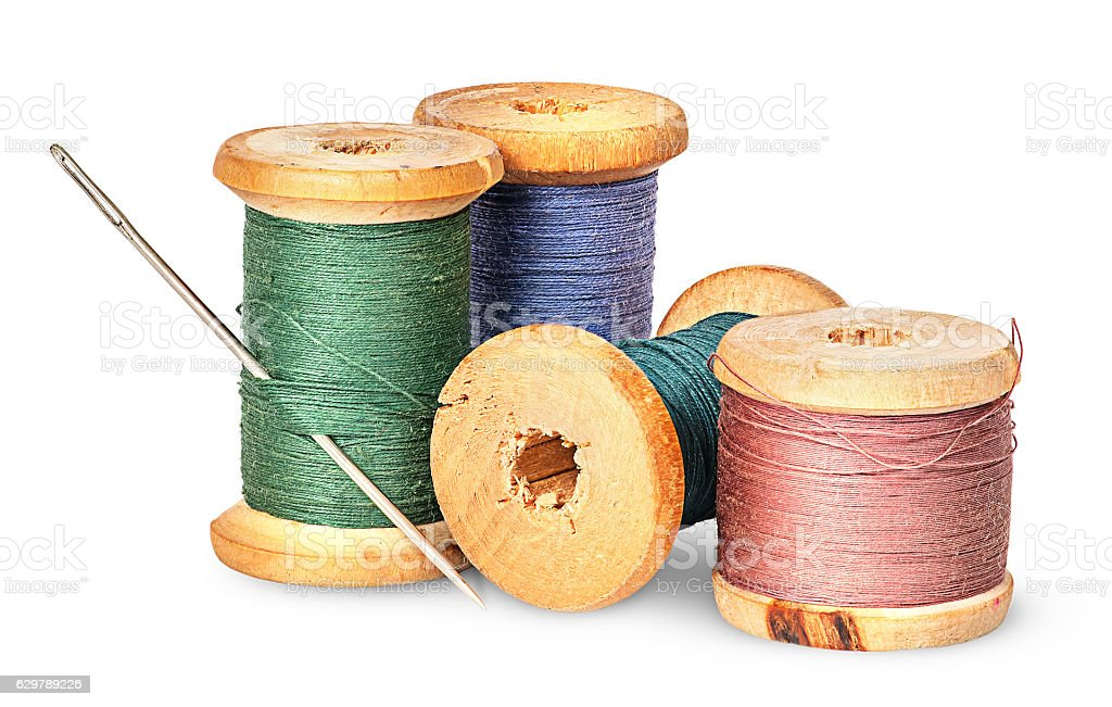 Needle and multicolored thread on wooden spool - Photo