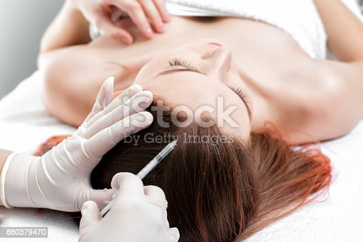 istock Needle mesotherapy. Cosmetic been injected in woman's head. 880379470